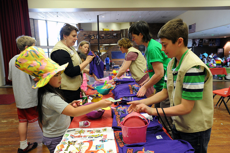 Eight-year-old Nadia Miller, left, purchased a raffle ticket from Jeremy Gordon at a gift and souvenir table set up during the Colorado Odyssey of the Mind's Longs Peak Regional Tournament on Saturday, March 24, 2012 at Berthoud High School.