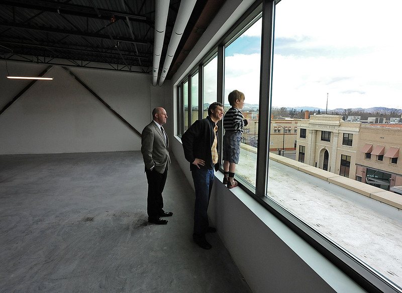 Troy Peterson, center, developer of the Rialto Theater Center, his son Henry Peterson, 4, and Joseph Palieri II, a broker with Realtec Commercial Real Estate Services, look out the window of the third floor of the Rialto Theater Center Thursday in downtown Loveland. Photo by Jenny Sparks