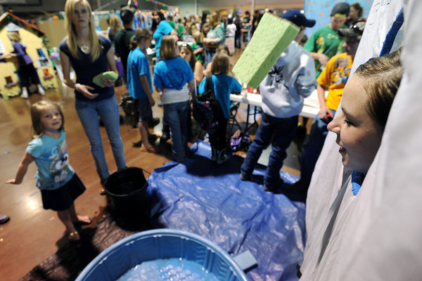 Jessica Conley, 15, right, braces for the impact of a wet sponge thrown by Elise LeVasseur, 6, left, at the Timnath Goal Diggers 4-H Club's Sponge Toss booth during the 4-H Carnival and Craft Show on Saturday, March 17, 2012 at The Ranch.