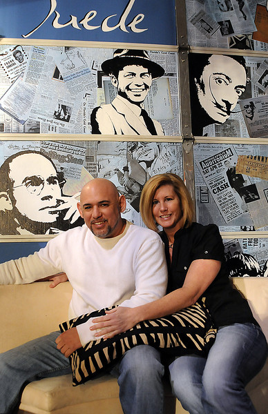 Roland Demers and Cassandra Breen, co-owners of the new Suede event center at  418 SE Eighth St., Unit B2, in south Loveland, pose in front of the garage door that was turned into a tribute to a number of cultural icons.