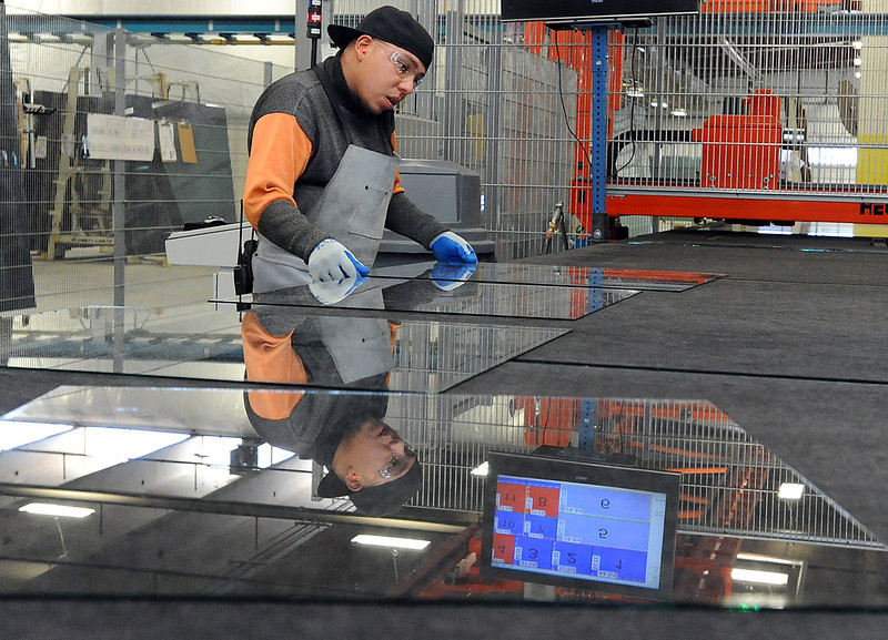 Adiran Moreno, an employee at Cardinal Glass in Loveland, separates glass at the break out table Thursday. The city of Loveland offered the company a small incentive package when they relocated here. Photo by Jenny Sparks