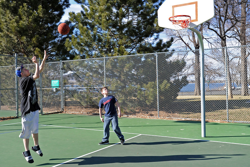 Jordan Dailey-Hawk, 11, right, looks on while Frankie Aleman shoots a jump shot while they were playing basketball together Tuesday afternoon at Dwayne Webster Memorial Park.