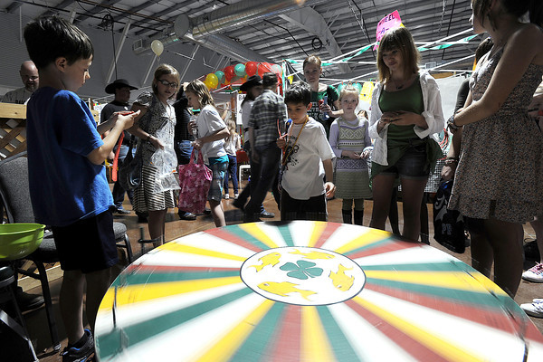 Asher Ricciardi, 8, left, runs the Rocky Ridge 4-H Club's Wheel of Fortune game as youngsters spin the wheel to win prizes during the 4-H Carnival and Craft Show on Saturday at The Ranch.