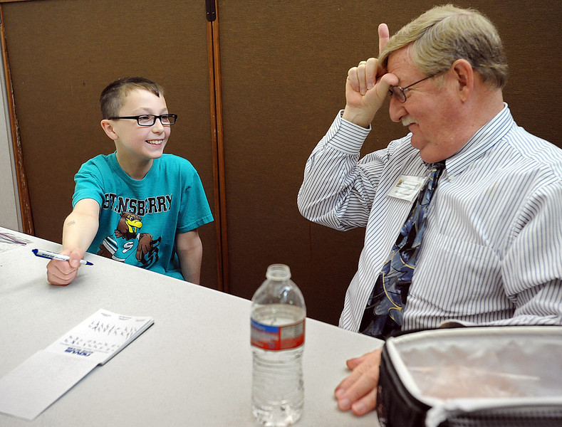 Stansberry Elementary School fourth-grader Quentin Eisele, 9, left, smiles as his mentor Ron Heusinkveld, right, proclaims himself as the loser after Quentin beat him during a dice game Tuesday at the school in Loveland. Heusinkveld is a volunteer from Immanuel Lutheran Church who mentors Quentin once a week during lunch time at school. Photo by Jenny Sparks