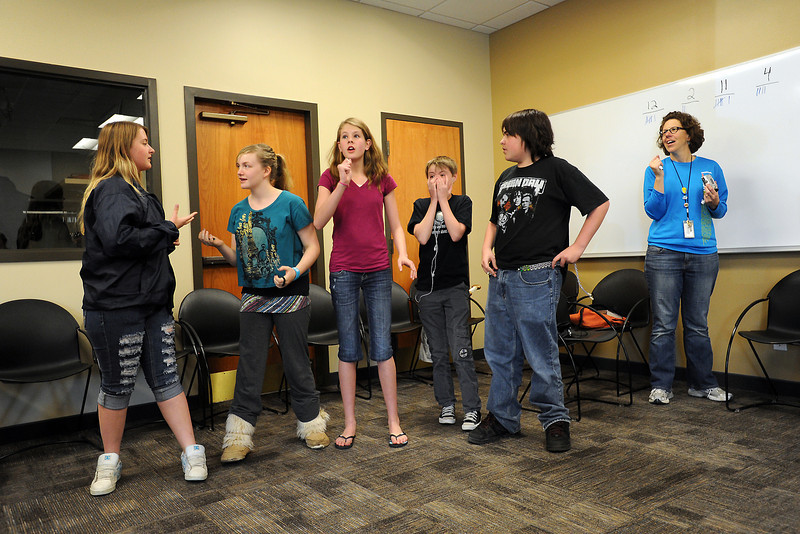 Loveland Public Library teen librarian Beth Gudmestad, right, looks on while members of Team 11, from left, Skylynne Dagel, 14, Danielle Carr, 14, Kierra Smith, 14, Otis McDonald, 13, and Brady Engleman, 14, discuss their team's answer while participating in a trivia contest Wednesday, March 21, 2012 at the library during a Hunger Games Party.