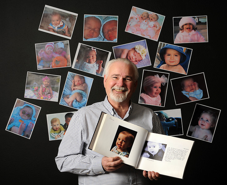 Loveland resident Ronald Stoddard, executive director of Nightlight Christian Adoptions, poses surrounded by photos of babies born through the Snowflakes Frozen Embryo Adoption and donation program that he created. Photo by Jenny Sparks
