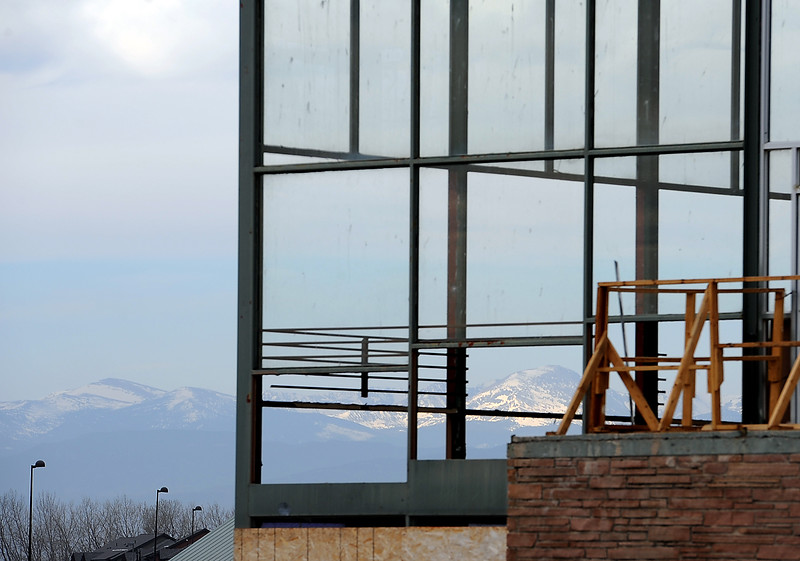 The mountains are framed by windows on the south side of the old Cloverleaf Kennel Club in Loveland Monday as crews work to demolish the building. The building has been a part of the landscape in Loveland since the 1950's. Photo by Jenny Sparks