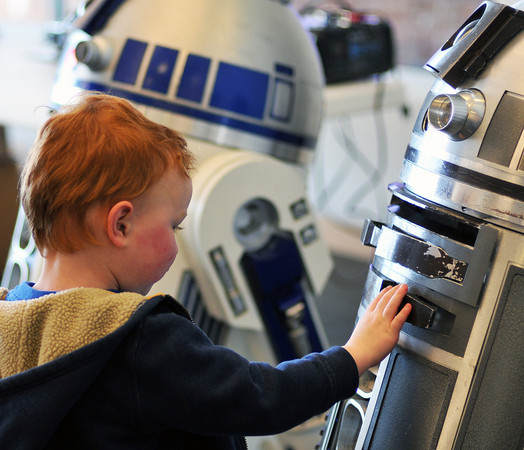 """031812_starwars_MAIN-1-MN.jpg Rylan Abbott, 3, of Loveland examines a """"talking"""" R2-D2 replica set up at the Rialto Theater before Sunday's showing of """"Return of the Jedi."""" He and his brother, Ian Abbott, 4, are Star Wars fanatics, their mother, Tara Hallahan said. (Photos by Madeline Novey)"""