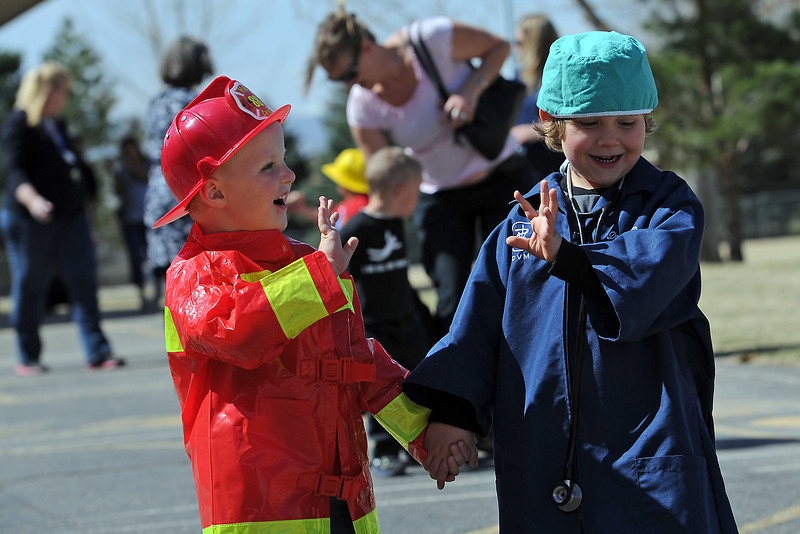 Preschoolers Titan Alps, 4, left, dressed as a fireman and Cole LeRoux, 5, dressed as a veterinarian walk together Wednesday, March 28, 2012 during a career march at Carrie Martin Elementary School.
