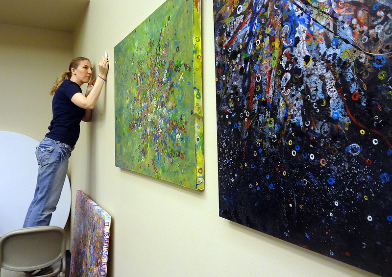 Angela Canada Hopkins hangs a series of paintings of cancer cell images Sunday at Pathways Hospice Center in Fort Collins. <br /> Photo by Jessica Benes