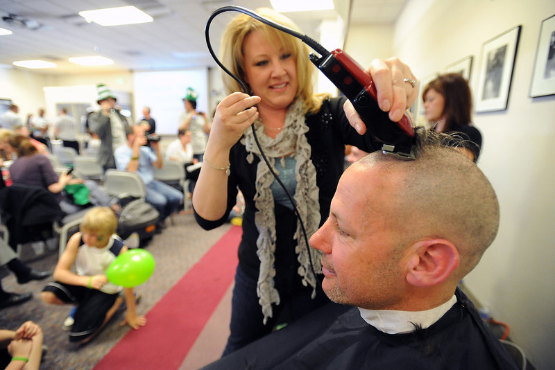 Loveland High School assistant principal Marc Heiser, front, has his head shaved by stylist Bethany McAllister at the Thompson School District administration building during a St. Baldrick's event Saturday to raise awareness and money to fund research for cures for cancer.