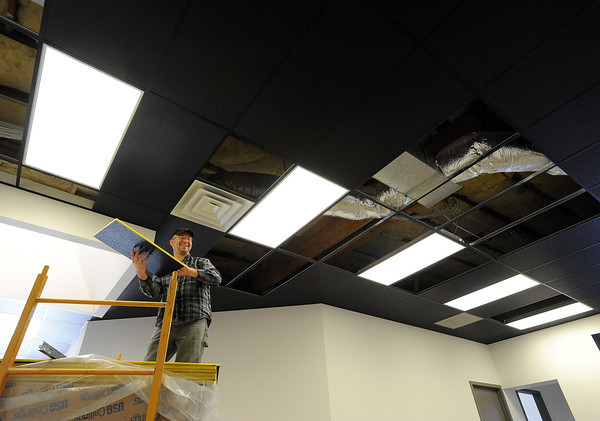 """0310 NWS ArtStudios-js.jpg Matt Thoen with ACE Acoustics shares a laugh with a co-worker while installing ceiling tiles Friday in a vacated building behind Aims Community College that used to house classrooms. The building is being renovated into 17 studio work spaces as part of the ArtWorks Loveland, Inc. project, supported by the Erion Foundation. ArtWorks Loveland is inviting artists to rent 15 of the studios for a year at a time as a way to enhance their careers through collaboration, coursework and events. The other two will be """"art-in-residence"""" spaces for two artists to work rent-free for 10 weeks at a time. Photo by Jenny Sparks"""