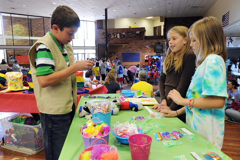 Jeremy Gordon, 11, left, assists Lizzy Fetzer, 9, and Camry Rowan, 10, as the girls purchase items on sale at Berthoud High School during the Colorado Odyssey of the Mind's Longs Peak Regional Tournament on Saturday.
