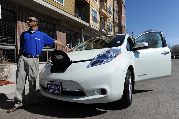 Tynan's Nissan internet director Jake Howard shows where the plug-in is located on a Nissan Leaf SV electric car as he explains its features during a stop in downtown Loveland for a Green Car Convoy.