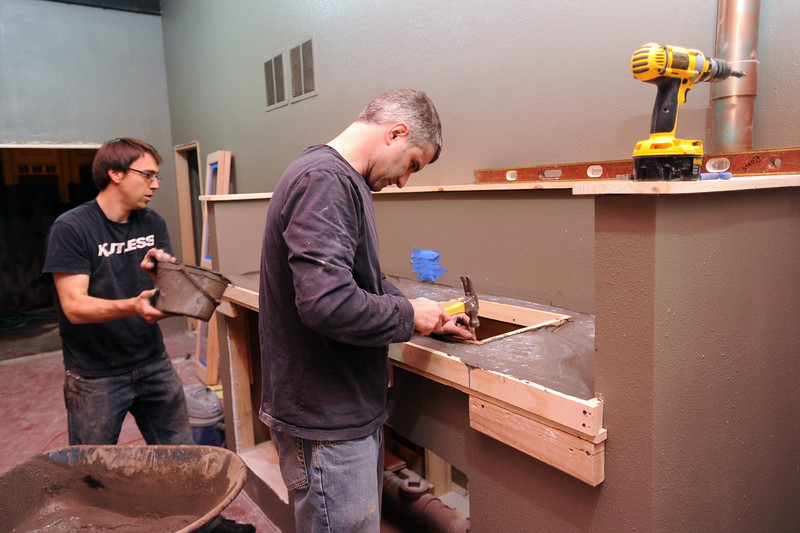 Jason Rohlf, right, and Mark Schreiber install a concrete countertop Tuesday evening in the kitchenette area of Rholf's new co-working business called The Armory at 411 N. Railroad Ave. in downtown Loveland.