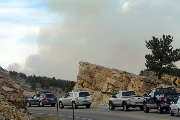 A plume of smoke from the Galena fire is visible in the distance as a line of cars waits on Friday, March 15, 2013 to continue on the road at the south end of Horsetooth Reservoir.