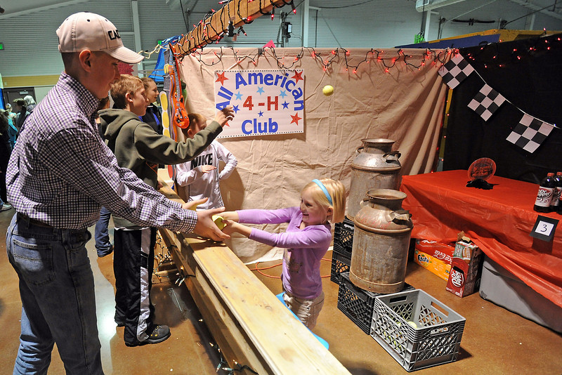 Stratton Wotowey, 13, left, and Tyler Pimple, 12, play a ball-toss game being run by Sam Dehaan, 10, back right, and his sister Zoey Dehaan, 7, from the All American 4-H Club during the 4-H Carnival and Craft Show on Saturday, March 23, 2013 in the First National Bank Exhibition Hall at The Ranch.