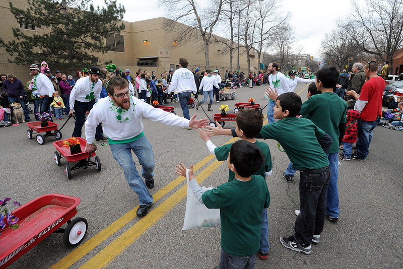 Parade watchers get high-fives while watching the Lucky Joe's St. Patrick's Day Parade on Saturday, March 16, 2013 in Old Town in Fort Collins, Colo.