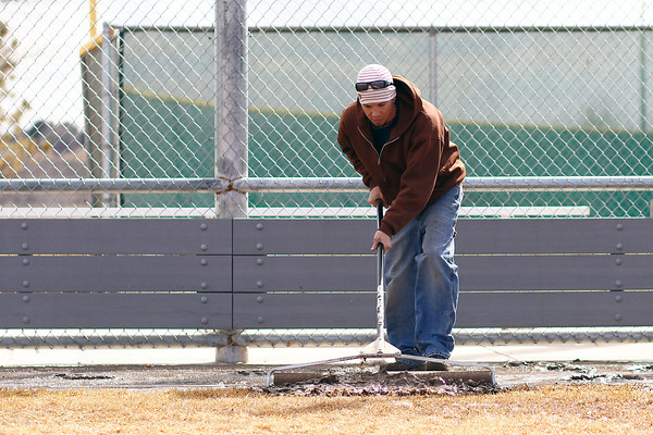 Trent McFadden pushes standing water into the grass Monday at Centennial Park and Ballfields in Loveland. Colo. With a baseball game scheduled on the field tomorrow, the park and rec crews are working hard to dry the field as much as possible.