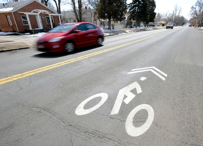 Vehicles zoom past new shared lane markings or sharrows, which indicate that cars and bicycles should share the lane near 13th Street and Garfield Avenue in Loveland on Wednesday, March 27, 2013. The shared lane markings are part of a pilot study the City of Loveland is testing for the first time. They will conduct traffic studies through the summer and decide whether or not to expand the markings to other streets.