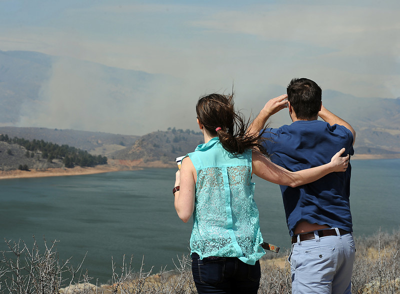 Jaryn Oakley, left, tries to steady Drew Wallace, right, agaisnt the wind as he takes a photo of smoke from the Soldier Canyon fire near Horsetooth Reservoir on Friday, March 16, 2013.