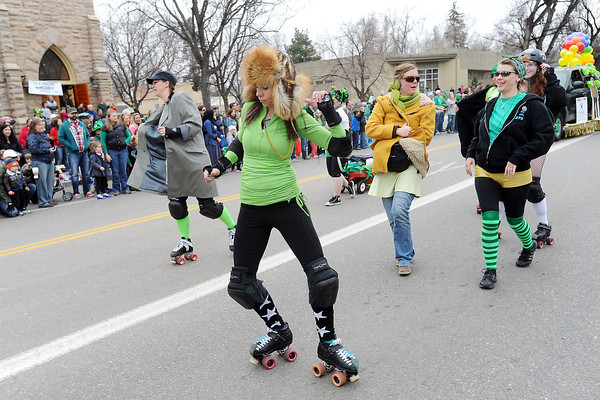 Members of FoCo Girls Gone Derby, front from left to right, Shaudin Kunselman, Tracey Bjick, Emilie Gooch, Kate Wyman and Stacey Kloxin roll and walk together along the parade route during the Lucky Joe's St. Patrick's Day Parade on Saturday, March 16, 2013 in Old Town in Fort Collins, Colo.