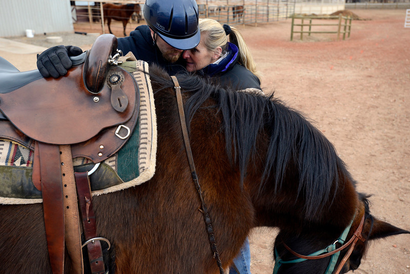 Volunteer Mary Cosens, right, and Tanner Salmon, a veteran who served in Iraq and suffers from post traumatic stress disorder, share a moment after a powerful theraputic riding session at Hearts & Horses west of Loveland on Friday, Feb. 8, 2013. Salmon participates in a program called Hearts & Horses for Heros, which helps veterans.