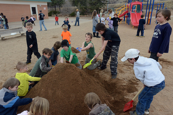 Youngsters pile sand to look like a volcano while playing together March 29, 2013 at Big Thompson Elementary School during a groundbreaking event for the school's new playground that's scheduled to open in August.
