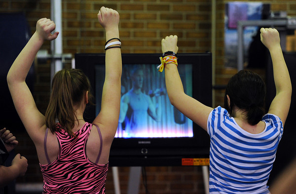 """Conrad Ball Middle School students Alicia James, left, and Mary Hinton follow along with an instructional exercise video Tuesday afternoon during the school's """"T-birds Gotta Run"""" after school program at Conrad Ball Middle School in Loveland, Colo."""