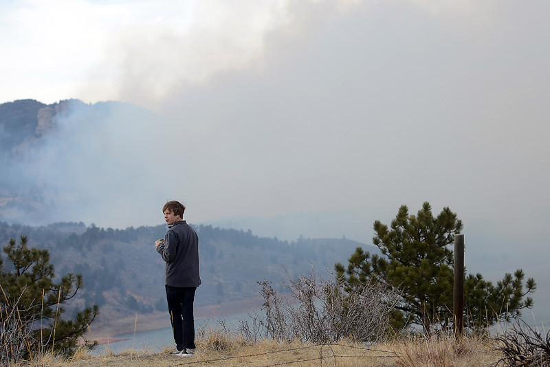 Windsor resident Zachary Brumley, 13, watches a plume of smoke from the Galena fire while standing on a hillside east of Horsetooth Reservoir on Friday, March 15, 2013.