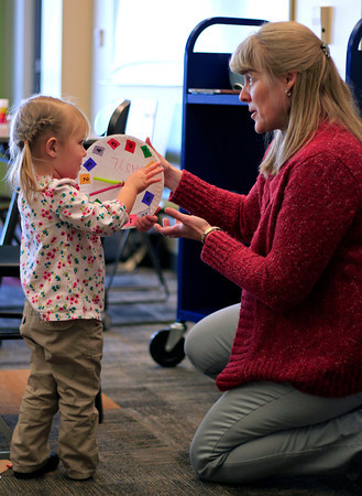Basyl Fillion, 2, shows her completed clock to librarian Kris Zimmerman Monday morning during Toddler Storytime at the Loveland Public Library in downtown Loveland, Colo. Ms. Kris, as she is known to the kids, has been conducting storytime for 28 years now.