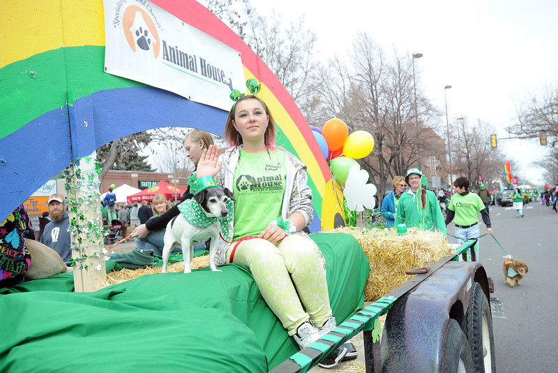 Alyssa Rodriguez sits with a dog named Tommy while riding atop the Animal House float during the Lucky Joe's St. Patrick's Day Parade on Saturday, March 16, 2013 in Old Town in Fort Collins, Colo. Tommy and the other dogs on the float are all available for adoption.
