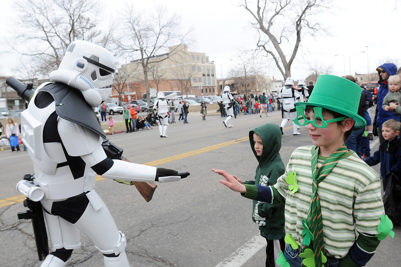 Riley Godbey, 8, front right, and Aidan Horwitz, 7, wave at a storm trooper while watching the Lucky Joe's St. Patrick's Day Parade together on Saturday, March 16, 2013 in Old Town in Fort Collins, Colo.