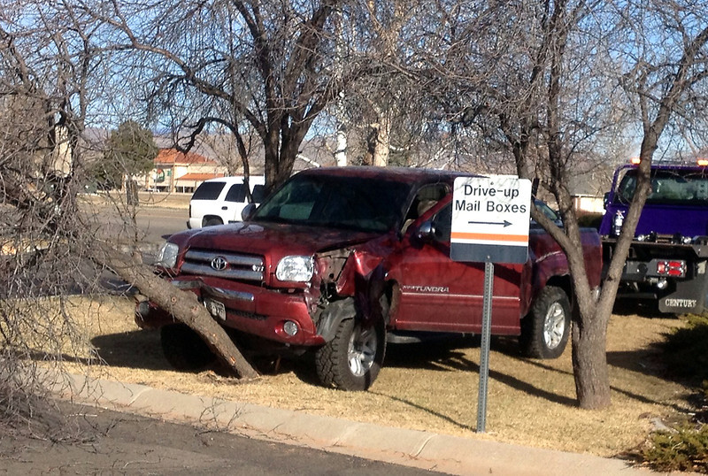 A towtruck driver prepares to move a Toyota pickup after it crashed into a tree at the Post Office on 29th Street in Loveland on Tuesday, March 19, 2013.