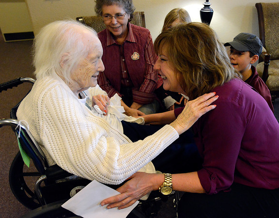 Carmy Jerome, assistant director at Aspen House Memory Care Assisted Living, reassures resident Darlene Manning, left, after she told Jerome she couldn't remeber where her money went while visiting with family in Loveland on Friday, March 8, 2013. Manning's daughter, Barbara Shoffner, and great grandkids, Emily Shoffner, 8, and Nicholas Shoffner, 14, look on in the background.