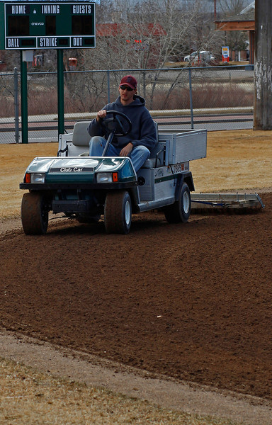 Zach Reynolds rakes the infield of the southernmost Centennial Park ballfield in Loveland, Colo, in hopes of speeding up the drying process Monday afternoon.