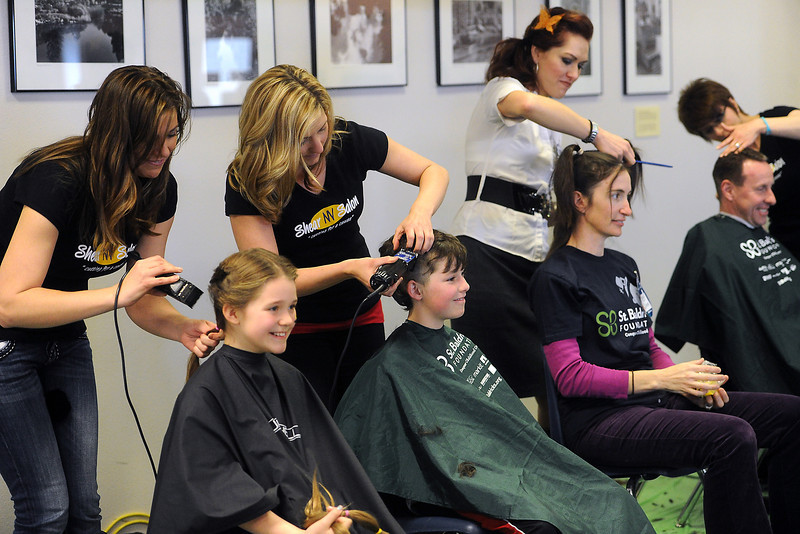 Shear NV stylist Shauna Payne, left, and other stylists cut all the hair off of shavees during the Community Resource and St. Baldrick's Event on Saturday, March 9, 2013 at the Thompson School District Administrative Building to raise money for childhood cancer research.
