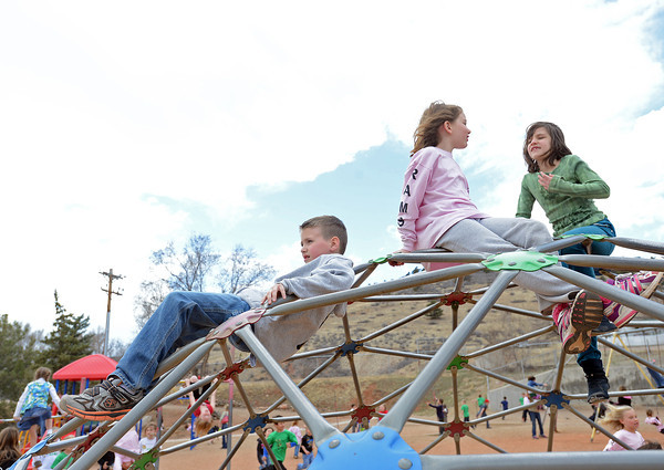 Wyatt Lindell, 7, left, Katelyn Wright, 7, and Lydia Fournier, 8, hang out together on the playground at Big Thompson Elementary School before a groundbreaking ceremony March 29, 2013 for the school's new playground that's scheduled to open in August.