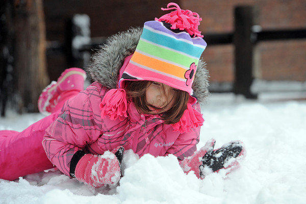 Six-year-old Giana Pascucci pushes snow into a pile after building a snowman Saturday afternoon outside her home in downtown Loveland.