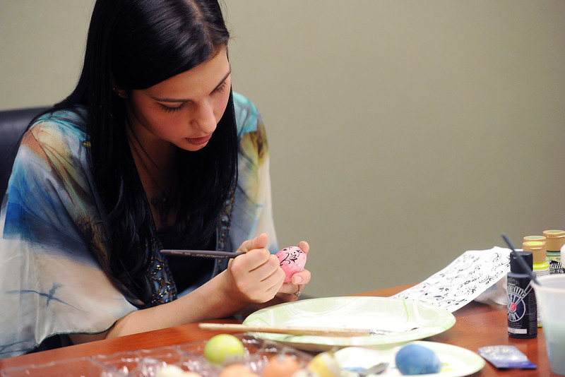 Monica Anselmo demonstrates how she decorates Easter eggs while painting a design Wednesday, March 13, 2013.