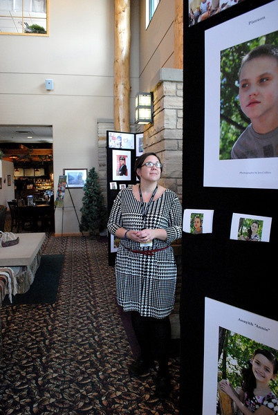 Chris Alsum, Executive Assistant of Group Publishing, admires Heart Gallery's pictures  located in the lobby of Group. By hosting this month long exhibit, she hopes to raise awareness about children in Colorado awaiting adoption.