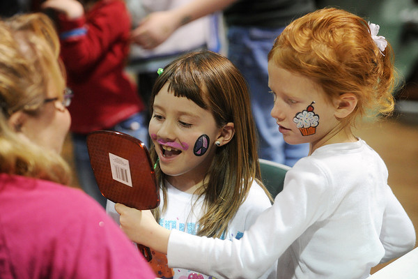 Moriah Blum, 5, right, holds a mirror for her friend Kadie Childers, 6, so they can see how their face paintings look that were done by Cristyn Johns, left, of the Boxelder Trails 4-H Club during the 4-H Carnival and Craft Show on Saturday, March 23, 2013 in the First National Bank Exhibition Hall at The Ranch.