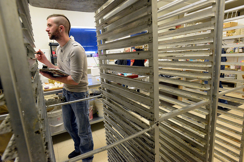 Brandon Giovannoni checks out bakers racks and other itmes up for auction at Schmidt's Bakery & Delicatessen in Loveland on Monday, March 25, 2013. Giovannoni is helping to start up a gluten free bakery in Lone Tree and was hoping for some good deals on equipment.