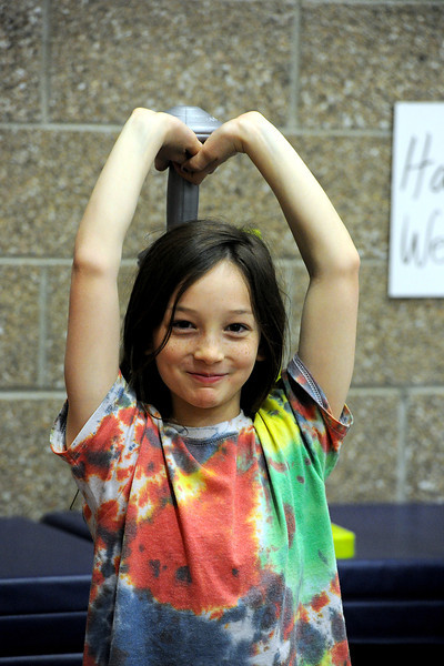 Ponderosa Elementery School fourth-grader Kylie Cook, 9, lifts weights during PE class at the school in Loveland on Wednesday, March 20, 2013.