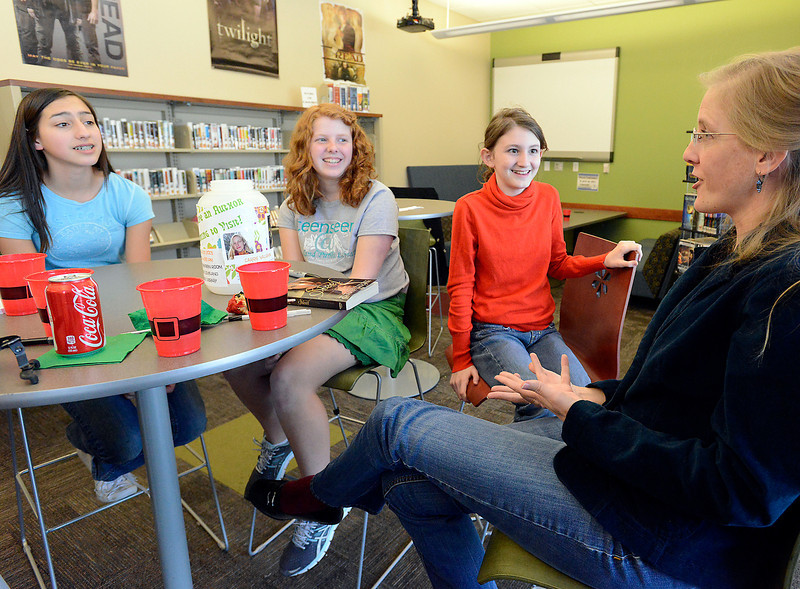 Loveland teens listen as Author Carrie Vaughn, far right, talks about her books and some of her writing techniques in the Teenseen room at the Loveland Public Library on Wednesday, March 27, 2013. Teens from left are Sophia Beall, 14, Drew Kline, 14, and Laina Eichmiller-Smith, 12.