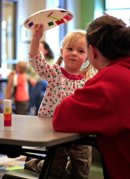 Basyl Fillion, 2, shows her completed clock to her mother Breanna Fillion during Toddler Storytime at the Loveland Public Library, Tuesday morning in downtown Loveland, Colo.