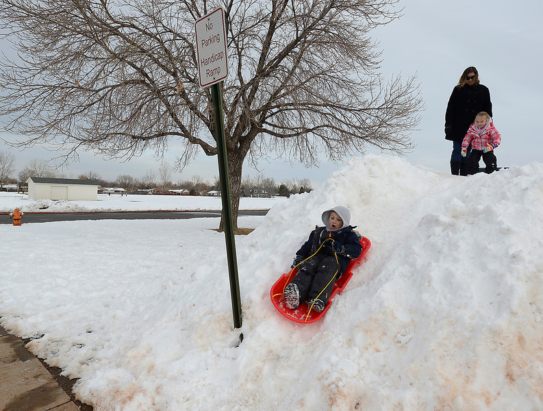 Aiden Combs, 5, sleds down a pile of snow after getting a good push from his sister Ava Combs, 3, as thier mom Kelly Combs watches at Conrad Ball Middle School on Thursday, Feb. 28, 2013 in Loveland.