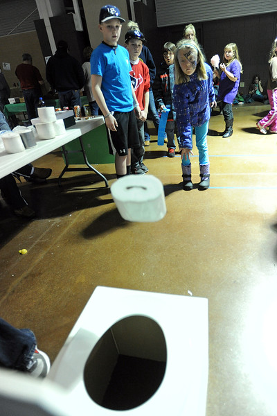 Raven Myhre, 10, front right, plays the Toilet Paper Toss game at the High Country Handiworkers 4-H Club's booth while Justin Phillips, 13, left, Hunter Walker, 12, and Zach Myhre, 8, look on during the 4-H Carnival and Craft Show on Saturday, March 23, 2013 in the First National Bank Exhibition Hall at The Ranch.