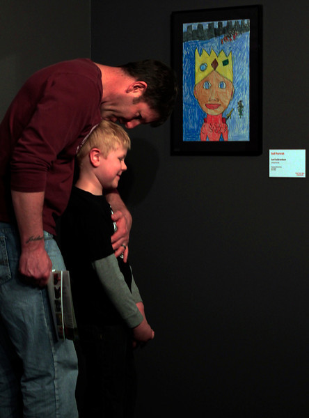 "Scott Gulbrandson leans over to embrace his son, Monroe Elementary first-grader Levi Gulbrandson (7), after Levi shows him his self portrait being exhibited at the Loveland Museum/Gallery's ""Look. Think. Make. Connect!"" annual Thompson School District art show, Sunday in downtown Loveland, Colo. Levi's lips were sealed as the two searched the gallery for his piece, as he didn't want to spoil the surprise for his father."