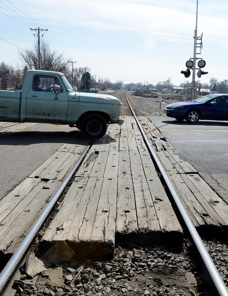 Cars stumble over the jarring railroad crossing between Cleveland and Garfield avenues on 10th Street in Loveland on Thursday, March 7, 2013. The crossing, along with three others, will be repaired in May.